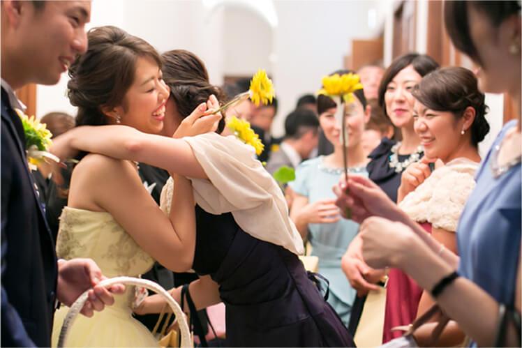 たくさんの友人に祝福され、そのうちの一人と抱き合う新婦